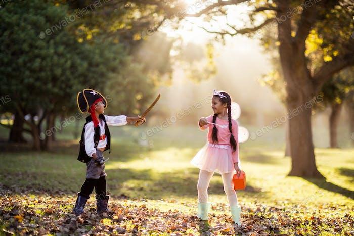 Playful siblings wearing costumes at park