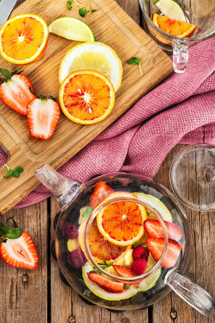 Fruit red tea with oranges and berries on wooden table, top view