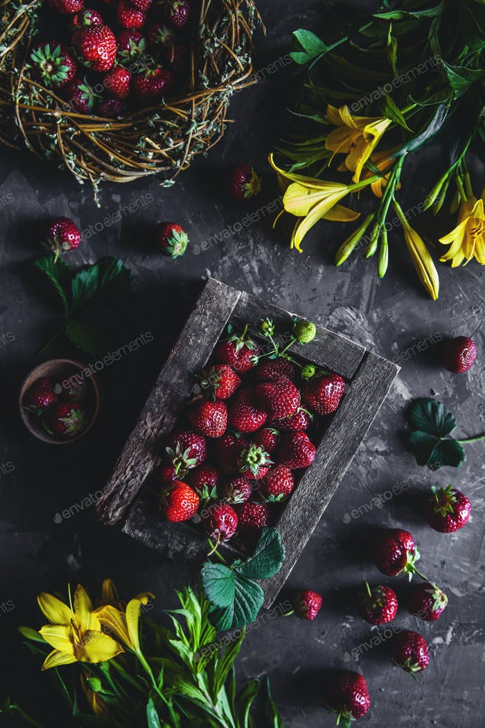 Fresh strawberries in an old box on a gray background with yellow flowers. Healthy food, fruit