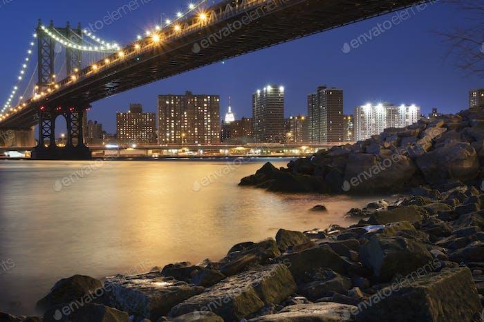 Vista nocturna hacia Manhattan desde Brooklyn, con el puente de Manhattan que abarca el East River.