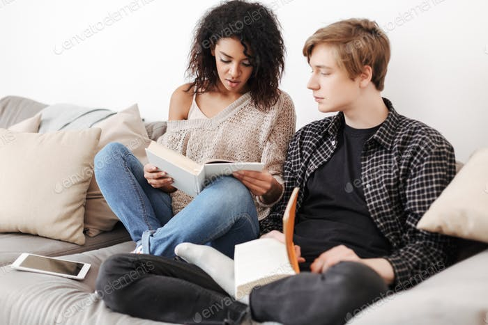 Young couple sitting on big sofa and reading books together at home