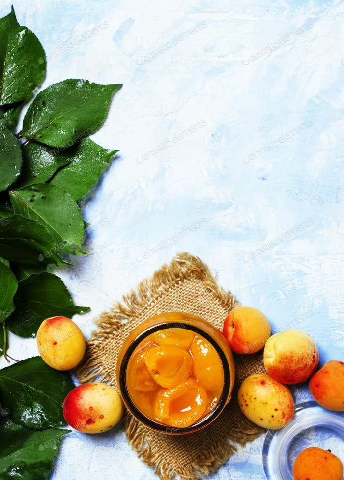 Apricot jam with fresh apricots with leaves