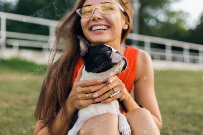 young happy smiling woman in orange dress having fun playing with dog in park