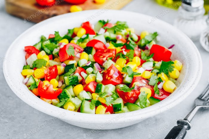 Fresh summer corn salad bowl with tomatoes, cucumbers, red onions and parsley.
