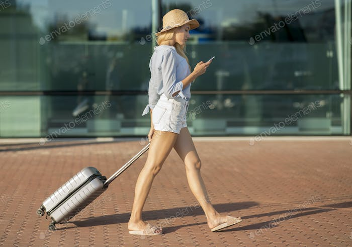 Female tourist walking with baggage near airport terminal