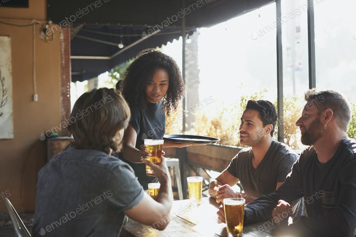 Waitress Serving Drinks To Group Of Male Friends Meeting In Sports Bar