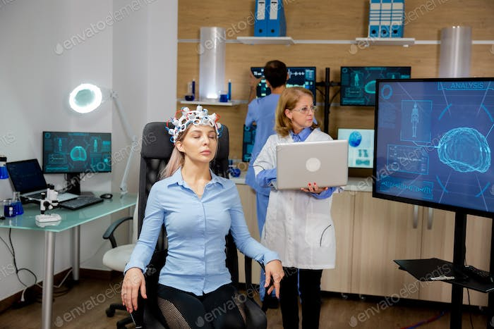 Doctor introducing some data into the laptop during a girl's brain scan procedure