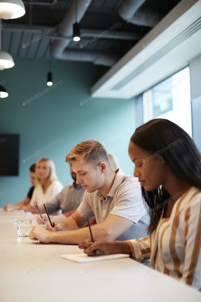 Grupo de jóvenes candidatos sentados en la mesa de la sala de juntas haciendo notas en la Presentación