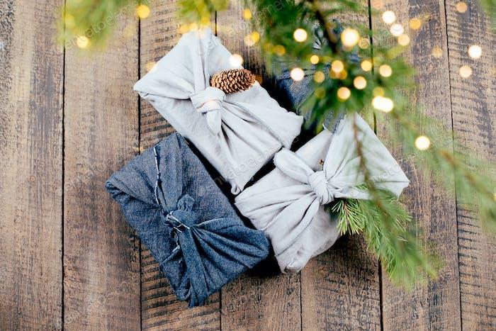 Weihnachten umweltfreundliches Gewebe wiederverwendbares Geschenk auf Holzboden. Ansicht von oben