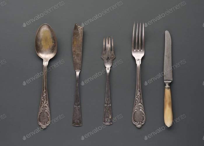 old scratched silver cutlery arranged in gray background