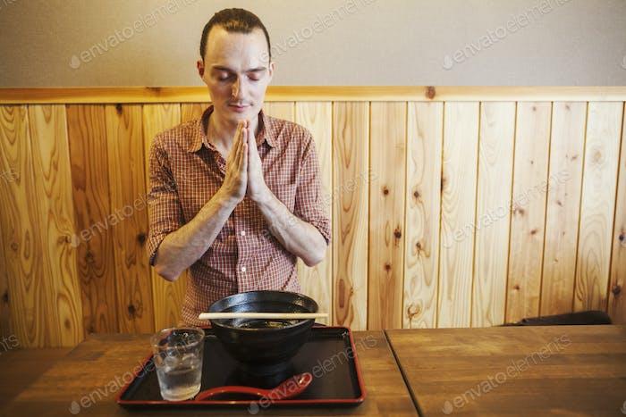 A western man in a Japanese restaurant saying a traditional Itadakimasu