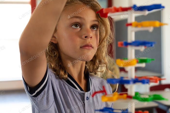 Close-up of mixed -race schoolgirl interacting with a DNA model in classroom at elementary school
