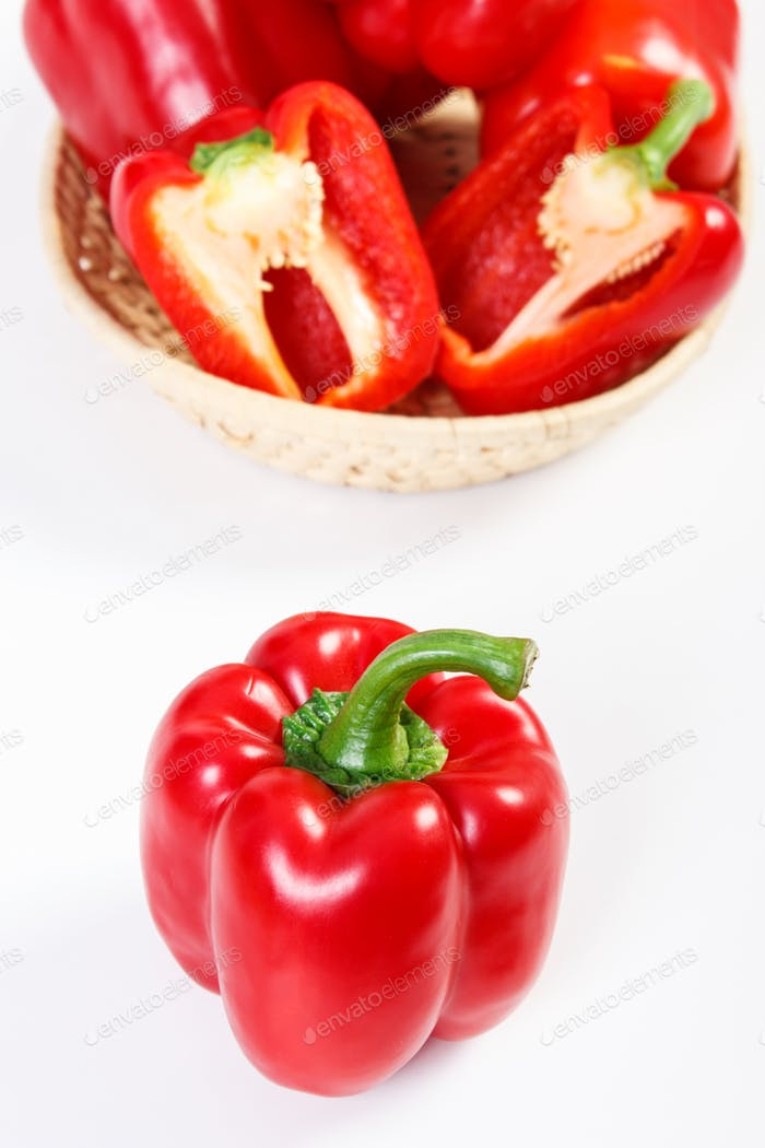 Fresh red peppers with wicker basket lying on white background, healthy nutrition concept