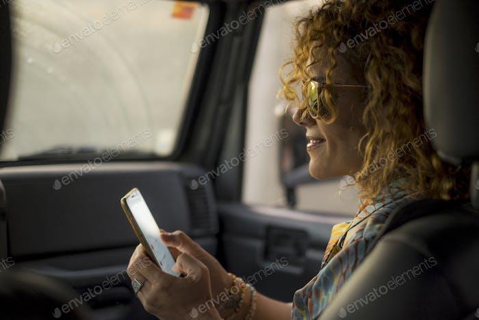 schöne Frau mittleren Alters Check Handy im Autositz
