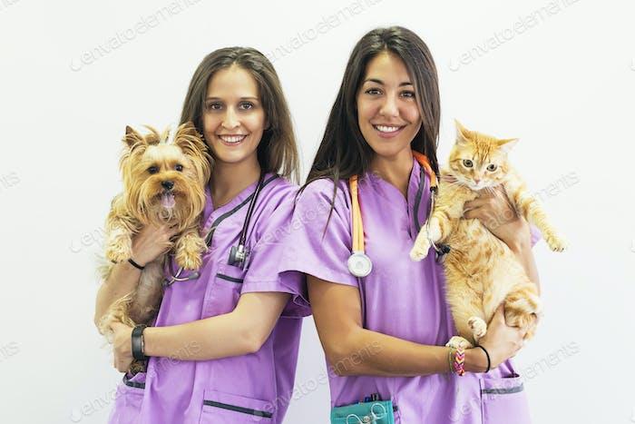 Cheerful women veterinary holding her pets.