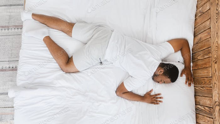 African Man Sleeping Lying On Stomach In Bed At Home