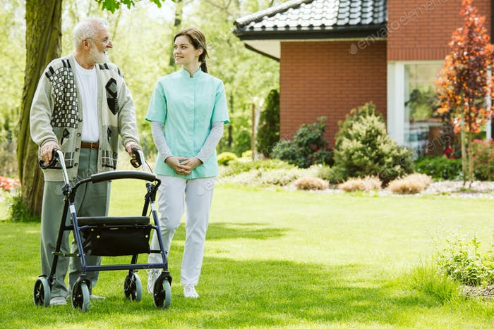Krankenschwester und Patient im Garten des modernen Seniorenhauses mit täglicher Pflege
