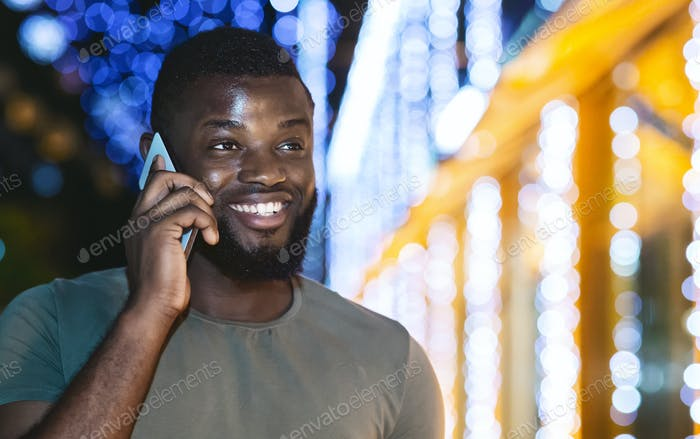 Black guy talking on phone, walking by night city
