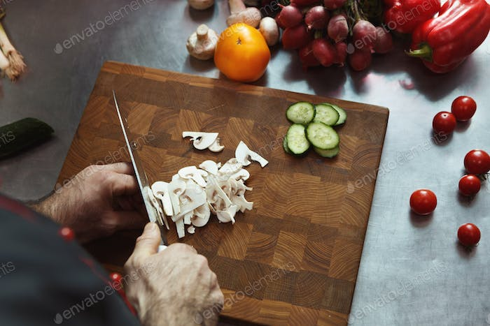 Chef cutting fresh vegetables for salad