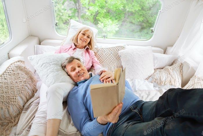 Alegre pareja casada relajarse en la cama y la lectura interesante libro dentro de camper van