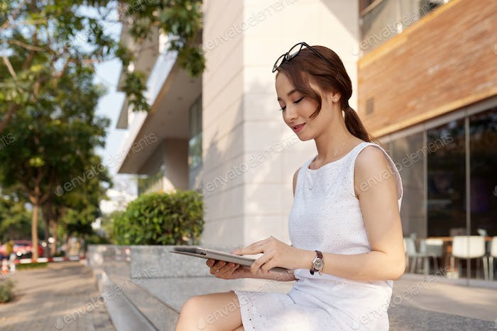 Smiling young woman reading data on tablet