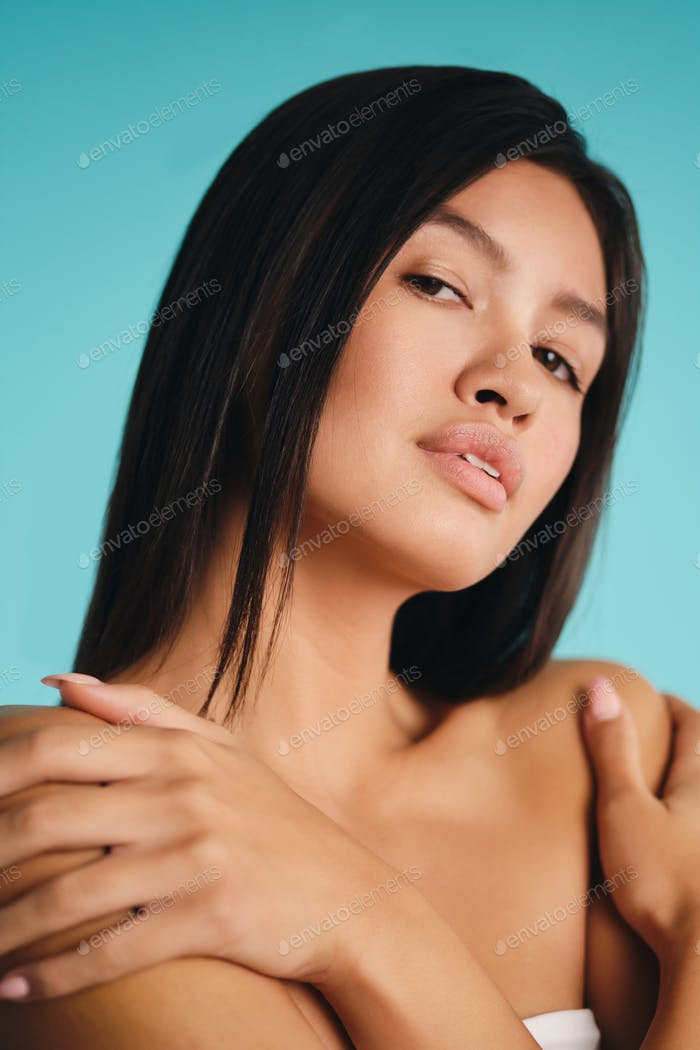 Close up gorgeous Asian brunette girl confidently looking in camera over colorful background