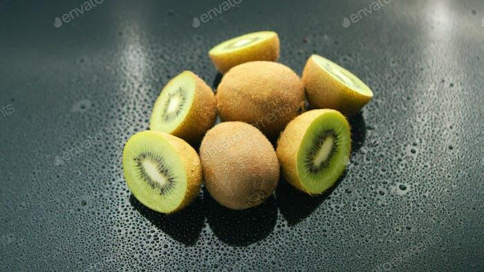 Whole and cut kiwifruit on table