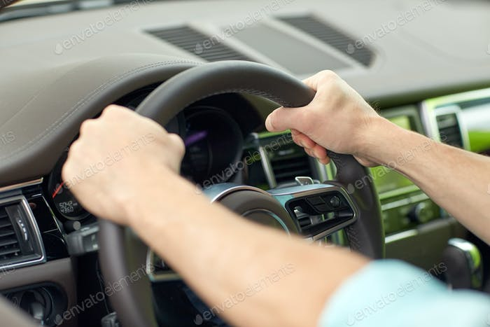 close up of male hands driving car