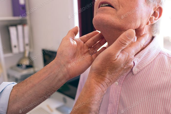 Mature male doctor checking senior mans neck in clinic at retirement home