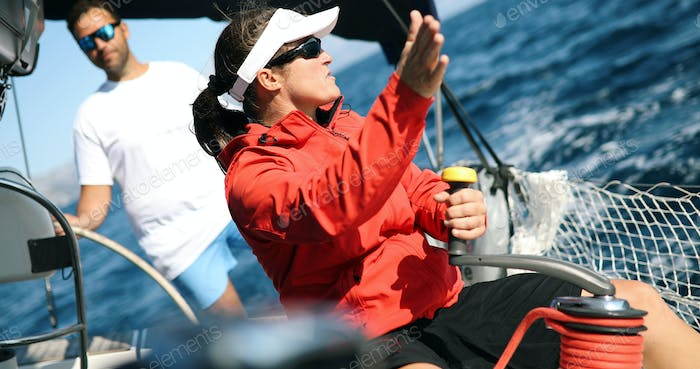 Young strong woman sailing the boat