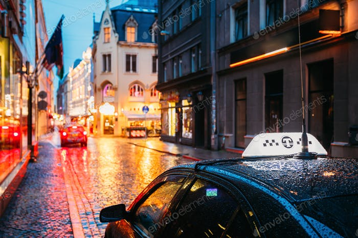 Taxi Car Wait Clients In Old European Streets  In Rainy Evening.