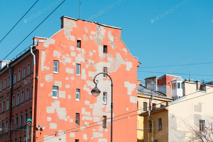 Old houses of European city. Walls of pastel colors with restoration spots.