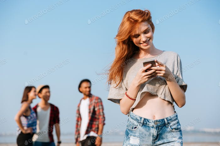 Smiling woman standing and using mobile phone near her friends