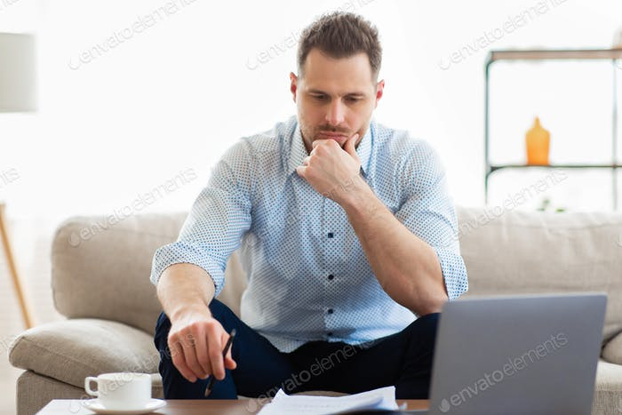 Pensive young guy sitting at table, looking at documents
