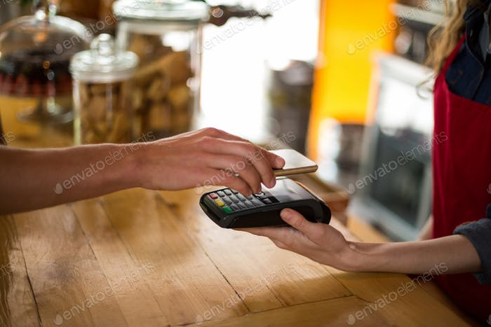 Man paying bill through smartphone using NFC technology