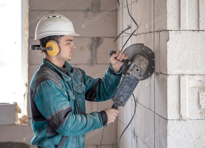 A handyman at a construction site works as a grinder.
