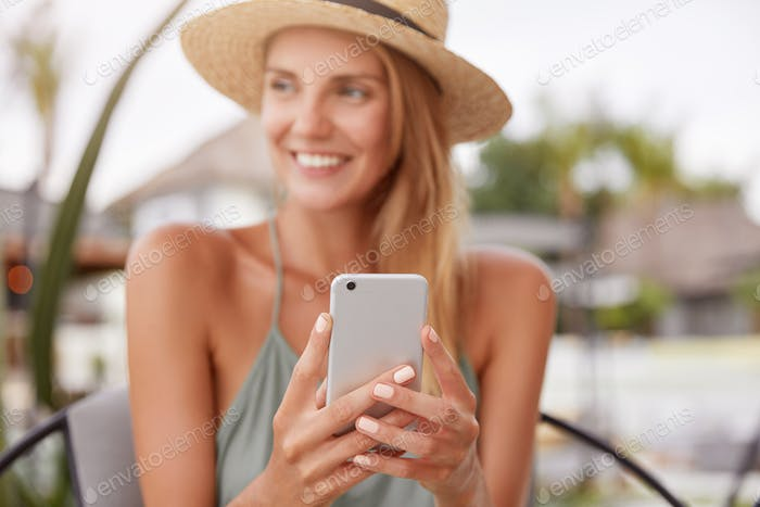Cheerful relaxed woman uses smart phone for chat with friends, sits in modern coffee shop or terrace
