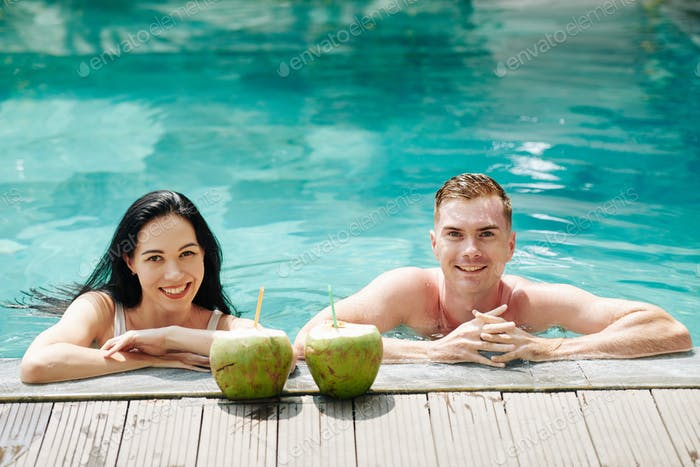 Smiling couple in swimming pool