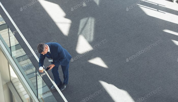 Businessman with coffee cup using mobile phone in modern office building