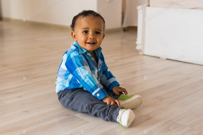 Small child tries to put on his shoes. Mixed race baby boy with shoes