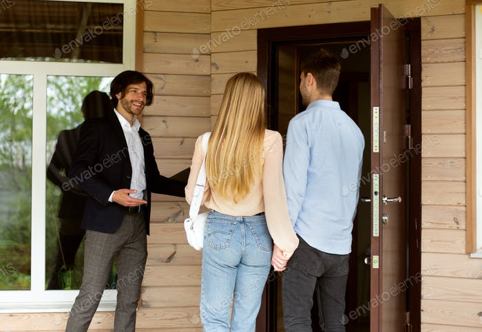 Property manager inviting potential buyers to enter house for sale