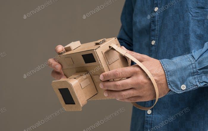 Photographer holding a cardboard camera