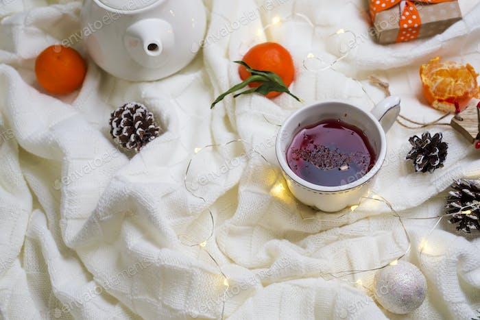Taza caliente de té con mandarinas y suéteres en la cama
