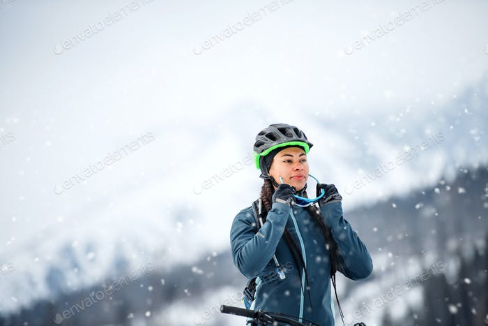 Weibliche Mountainbiker mit Fahrrad im Freien im Winter Natur stehen.