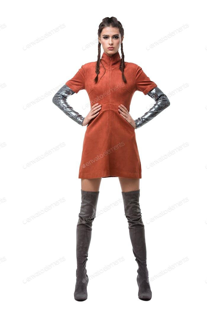 Junge schöne Dame stehend in hellbraunem Kleid und kniehohe Stiefel auf weißem Hintergrund