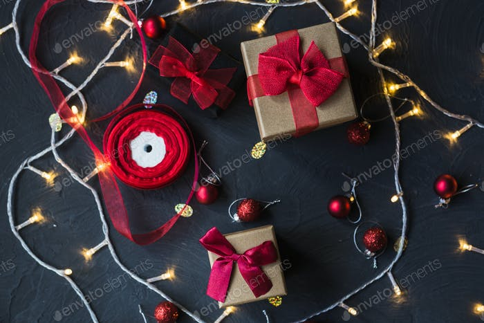 Christmas gifts boxes with red bow and ribbon on a black backround.