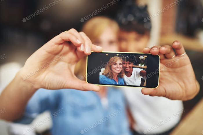 Two women friends taking a selfie on a mobile