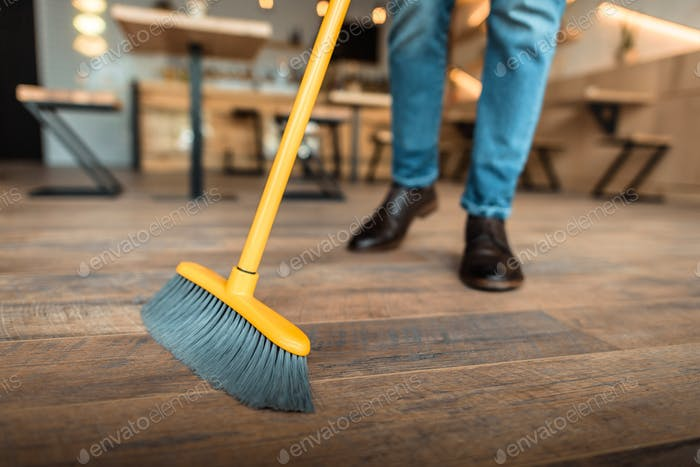 cropped view of african american worker sweeping with broom in coffee shop