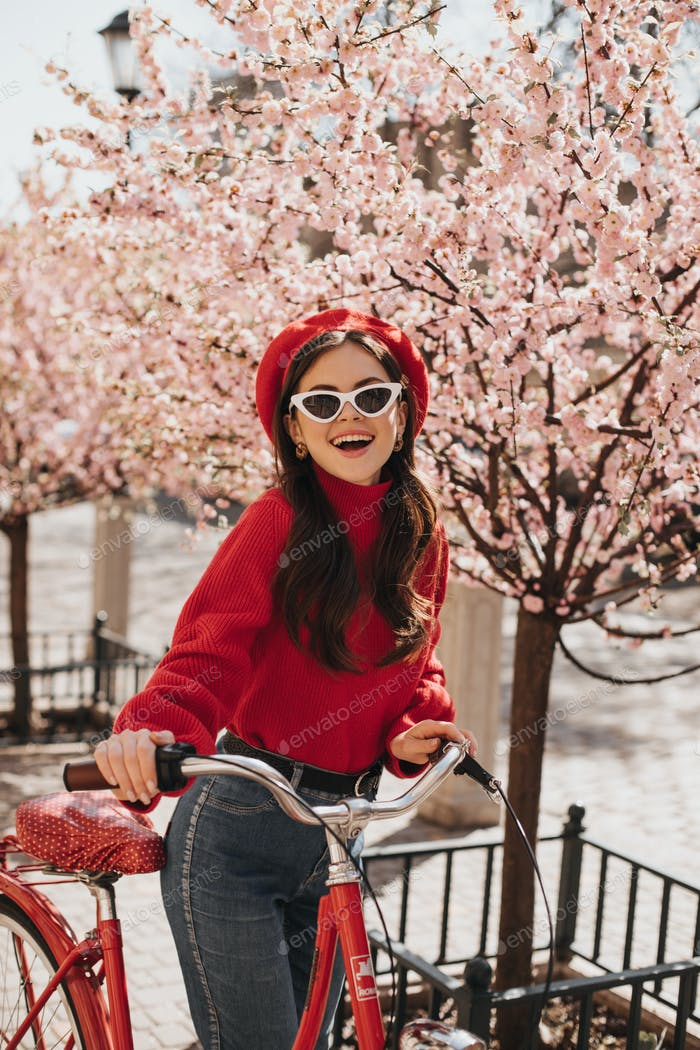 Portrait of woman in sunglasses and red outfit posing with bicycle on street. Young lady in beret a