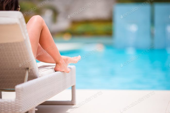 Woman sunbathing on a lounger at tropical resort near pool